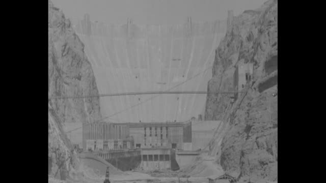 """vídeos de stock, filmes e b-roll de """"boulder dam a symbol - roosevelt"""" over black screen then superimposed over boulder dam / aerial of dam with lots of cars and people on it / sot... - represa hoover"""