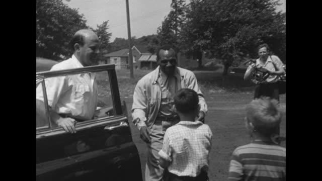 boxing superimposed over two men boxing in ring / jersey joe walcott lifts up boy after getting out of car / he walks with arm around boy followed by... - heavyweight stock videos and b-roll footage