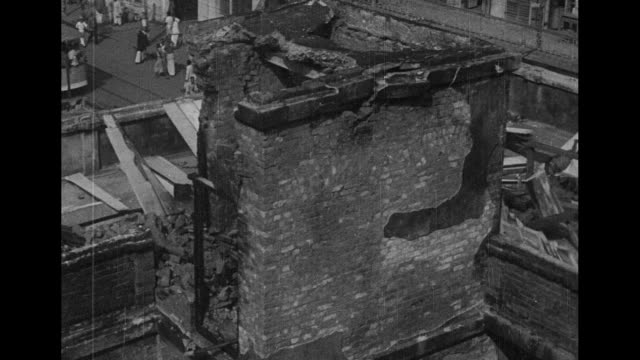 vídeos de stock e filmes b-roll de calcutta air raids superimposed over rising or setting sun / two overhead shots of damaged buildings / overhead shot of people in street below pan... - calcutá