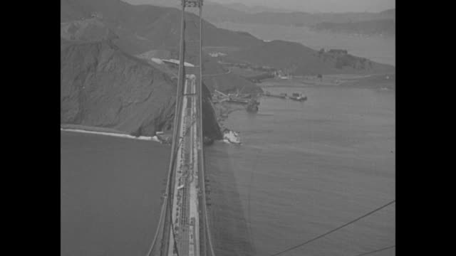 california superimposed over ws golden gate bridge al / shot from top of bridge tower of bridge below / construction workers at work on top of bridge... - golden gate bridge stock videos & royalty-free footage