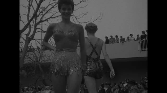 "title ""california swim styles for 1952"" superimposed on high angle view of fashion show / woman in ""peter pan"" inspired bathing suit decorated with... - one piece swimsuit stock videos & royalty-free footage"