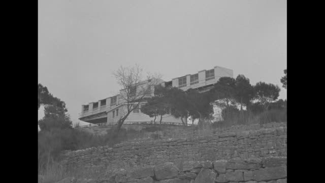 "vídeos de stock e filmes b-roll de ""cannes"" superimposed over view from below of solarium for tuberculosis patients sitting atop hill / view of solarium through windshield of car... - 1930"