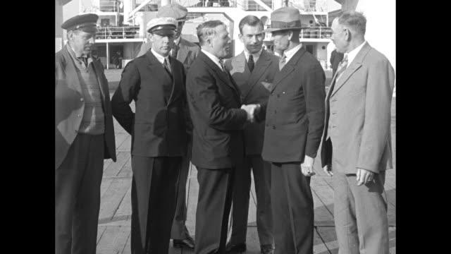 capt bob bartlett arctic explorer congratulates capt neilson and his gun crew / bartlett on deck of whaler sir james clark ross with captain and crew... - arpone video stock e b–roll