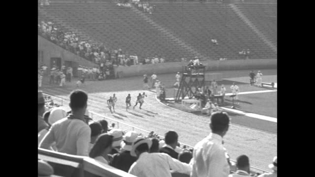 '100 Meter Dash Heat One Metcalfe winner Heat two Simpson winner' / Spectators rise to their feet in foreground as 100 meter dash race begins pan to...