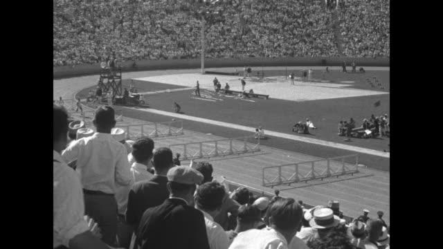 110 meter hurdles won by saling us no 456 time 0146 / audience in stands stand up as racers begin running and jumping hurdles pan as racers reach... - オリンピックスタジアム点の映像素材/bロール