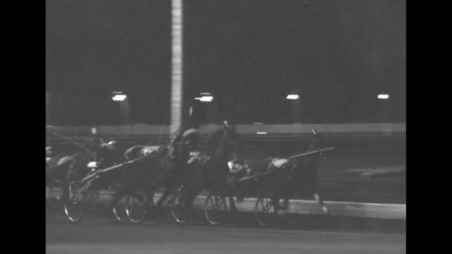 $25000 trotting classic superimposed over night harness race at roosevelt raceway / horses behind motorized starting gate / gates arms fold in / race... - starting gate stock videos and b-roll footage