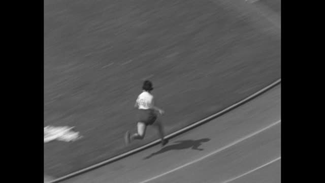 '400 Meter Relay Women Won by US Time 047 New World's Record' / runner in starting block runs catches other runners they hand off wand three times...