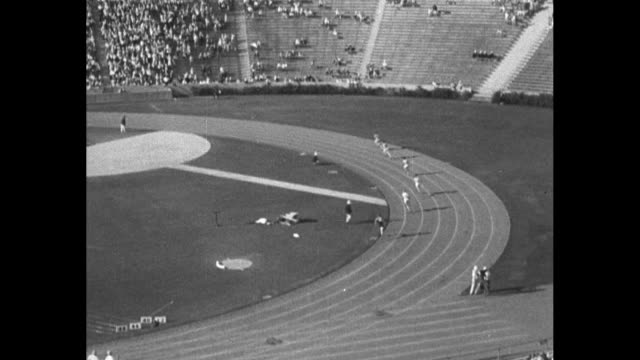 '400 Meter Run Final Won by Carr US No 408 Time 0462 New World's Record' / WS runners round curve of track / audience in stands stand up / MS William...