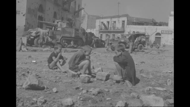 """5th army enters naples"" / vs tanks and trucks roll down road and past camera, tanks and trucks also parked along roadside / tank rolls past rubble /... - world war ii video stock e b–roll"