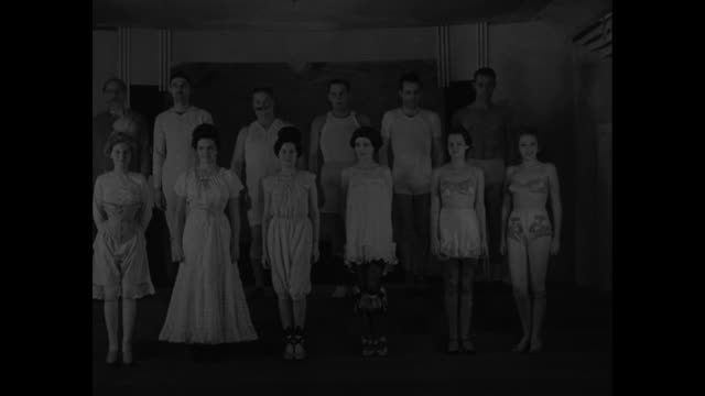 a subject that's close to us all / row of male models in underwear comes up stairs at chicago's merchandise mart and stops row of female models in... - 1936年点の映像素材/bロール