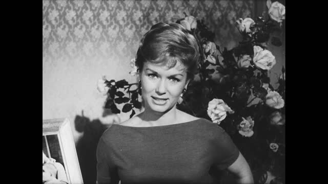 """visit with debbie reynolds""""; debbie reynolds in front of flowers, talking to the camera about child cancer, holds up a framed photo of woman holding... - debbie reynolds stock-videos und b-roll-filmmaterial"""