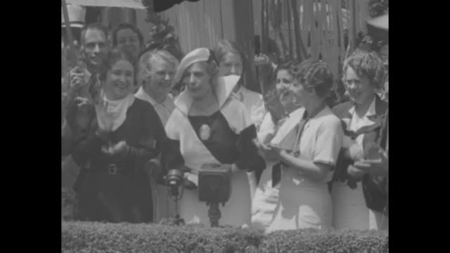 """aimee denies romance"" / men and women march down street with parasols raised over heads past crowds and some houses / aimee semple mcpherson stands... - sonnenschirm stock-videos und b-roll-filmmaterial"