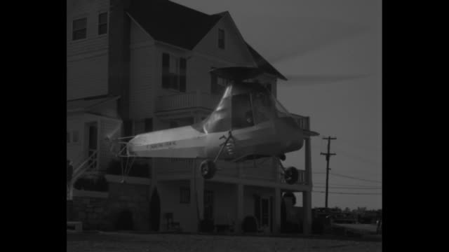 air flivver new helicopter is future's family car / frank piasecki carries golf clubs as he walks down back outdoor steps of house with woman pan he... - gas station attendant stock videos and b-roll footage