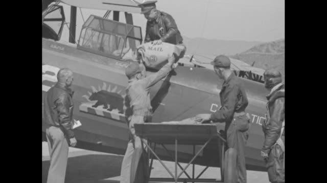 """""""air mail problems!"""" / two shots of men loading airmail bags into airplane / four aerial shots of airmail planes flying in formation / secretary of... - 航空便点の映像素材/bロール"""