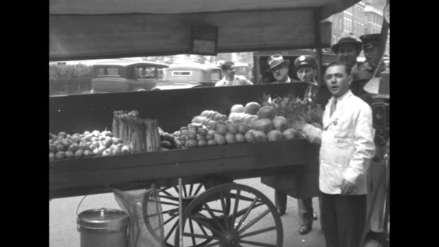 Al Smith Lauds Peddler For Prize Pushcart John Ruggieri gets medal from Outdoor Cleanliness Association / pan street scene in probably Brooklyn with...