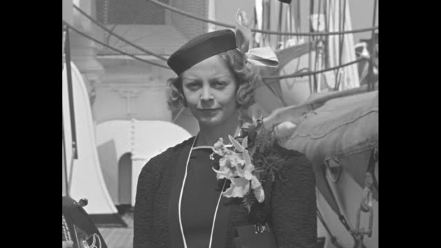 'Alice Marble Babe Ruth in sports news' / 'Alice Marble' superimposed on tennis player Alice Marble and cameramen aboard ship / VS Marble wearing hat...