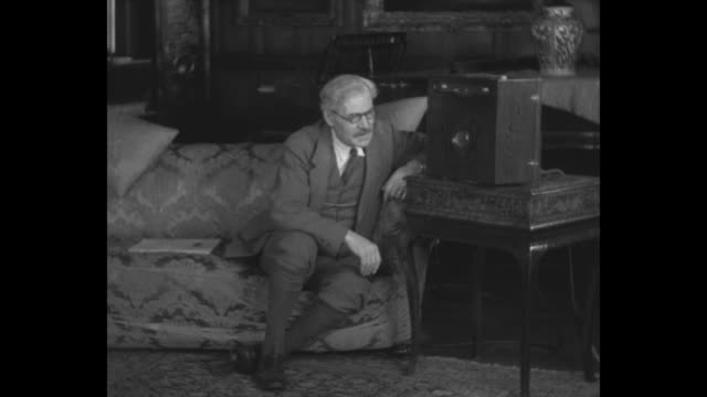 all england listens to her royal salesman premier ramsay macdonald hears prince's voice from faraway argentine / macdonald sits on sofa listening to... - radio stock videos & royalty-free footage