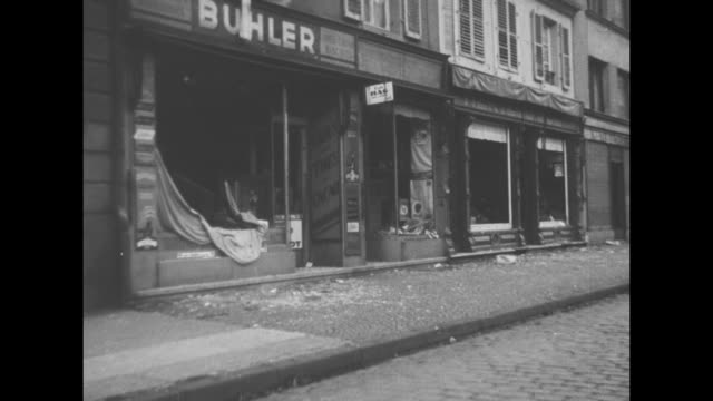 "vidéos et rushes de ""all quiet, allies watchful on west front"" / view of the sarreguemines skyline / vs deserted street; blown-out windows of ""buhler"" store; damaged... - seconde guerre mondiale"