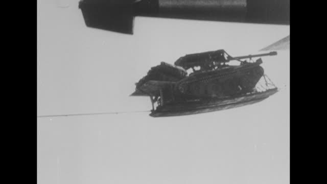 vidéos et rushes de amazing paradrop selfpropelled antitank gun superimposed over armored antitank gun with a pan right / parachutes open behind aircraft / aerial view... - anti aérien