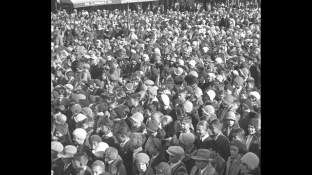 """title card """"america the beautiful"""" / pan across large crowd of schoolchildren gathered in large outdoor area / title card: """"mayor carriere sees... - 1920 1929 stock videos & royalty-free footage"""