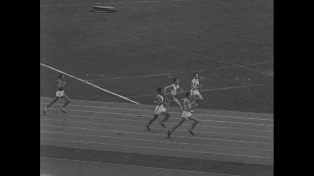 america's olympic winners superimposed over men's track event at 1936 summer olympic games in berlin with jesse owens running for the us / ws olympic... - salto in lungo video stock e b–roll