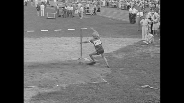 """""""and now meet babe didrikson 'one-girl track team'"""" / babe didrikson does high jump at outdoor track and field event / starting pistol fires, vs... - 女子トラック競技点の映像素材/bロール"""