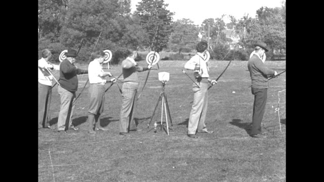 'Archers meet in tournament Newton Mass bow strips wand and arrows whizz as archers try skill' / VS line of men and boys aiming shooting at...