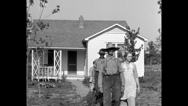 Arkansas Colony Hails First Lady / family members walking down walkway in front of house / group of large family father and sons wave hats / view...
