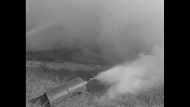 """army teaches men war uses of chemicals"" / line of soldiers wearing gas masks fire cylinders of chemicals, with white clouds emitting from the... - 起爆装置点の映像素材/bロール"