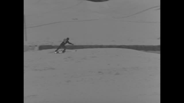 austrians star at intnat'l ski meet superimposed over snowy mountains pan to people at top of ski trail / ms skier skiing past camera and down hill /... - slalom skiing stock videos & royalty-free footage