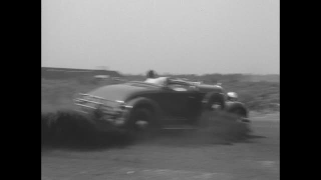 autos skid and crash pete de paolo does spectacular spins to show danger of skidding / 1931 desoto convertible speeds around track kicking up dust /... - prova di collisione video stock e b–roll