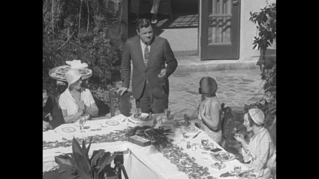 Babe Ruth now perfect 38 in age not size Bambino cuts birthday cake for wife and friends at St Petersburg Fla / overhead shot of Babe Ruth and guests...