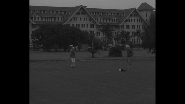 Ball Czar Finds Golf Above Par / LS of man golfing hotel in background / baseball commissioner Kenesaw Mountain Landis putts with friends Wells...