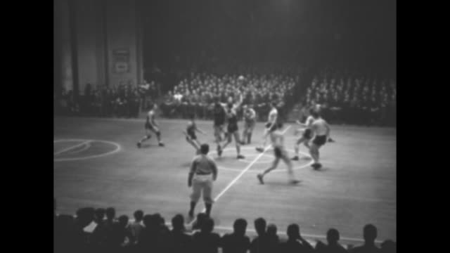 """title card: """"new york"""" superimposed over jump ball beginning basketball game between city college of new york in black, and providence college in... - shooting baskets stock videos & royalty-free footage"""