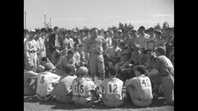 vídeos de stock e filmes b-roll de be a babe ruth / group of wouldbe baseball players gathered around max carey formerly of the brooklyn dodgers / cu carey / baseball student runs to... - camisola de basebol