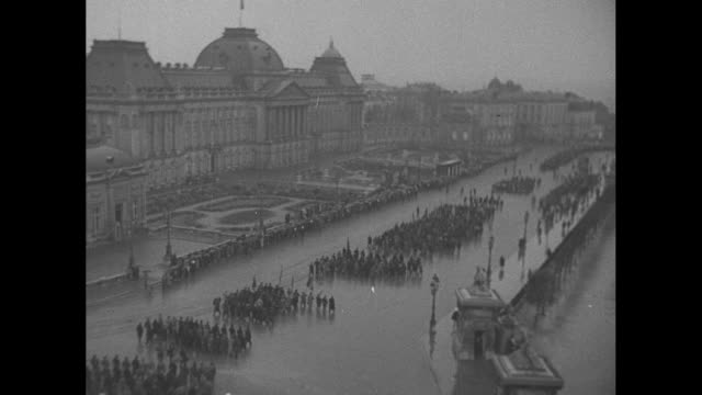 'Belgians Riot As The King Holds Review' / title 'Brussels' superimposed over Belgian war veterans marching toward camera on rainy street / montage...