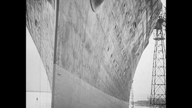 biggest ship ss normandie launched at st nazaire brings france sea supremacy / pan down bow of ocean liner ss normandie in dry dock / cu bottle... - dry dock stock videos & royalty-free footage