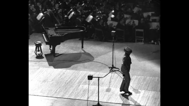 bill robinson, the inimitable / tilt-down shot spotlights shine on darkened stage as african-american tap dancer bill robinson dances at a show to... - tapping stock videos & royalty-free footage