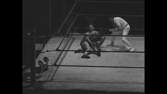 'Black Eye for Referee in Mat Bout' / VS high angle views of wrestling match between Joe Savoldi and Danno O'Mahoney VS man getting knocked out of...