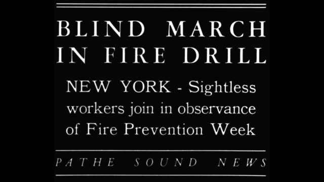 blind march in fire drill new york sightless workers join in observance of fire prevention week / line of blind people touching backs of blind people... - allarme di prova video stock e b–roll
