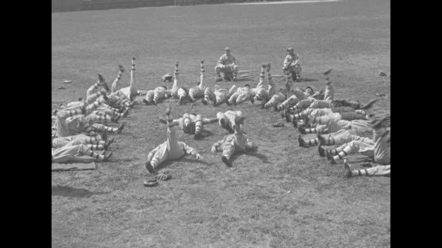 boston braves on warpath for pennant / team in uniforms run across field / ws they lie in semicircle doing leg lifts roll up and do bicycle exercise... - semi circle stock videos & royalty-free footage