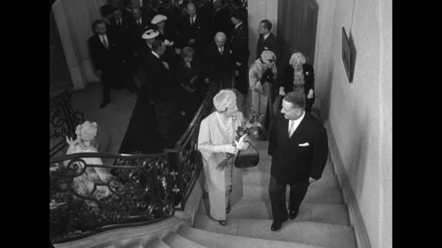 title card britain's queen mother opens paris exhibit / the queen mother carries bouquet of flowers up stairs / cu queen mother carries flowers into... - präsentation hinter glas stock-videos und b-roll-filmmaterial