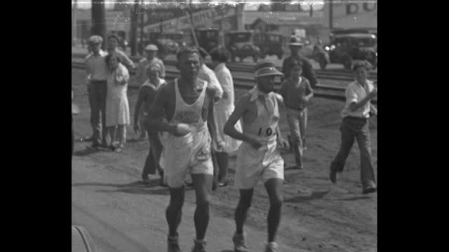 """bunion racers reach pacific, los angeles - weary dogs bear owners on last lap of run from new york"" / with oil derricks beyond, walking men follow a... - 1920 1929 stock videos & royalty-free footage"