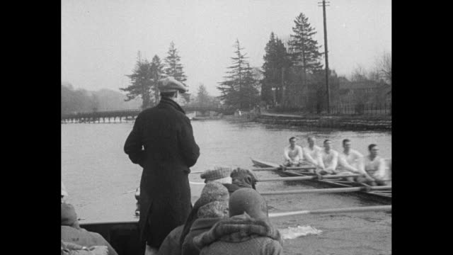 """""""cambridge crew mans the sweeps - henley, eng. - light blues take first practise row on historic thames in training for oxford clash"""" / man in coat... - oxford england stock-videos und b-roll-filmmaterial"""