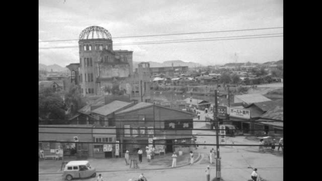 vídeos y material grabado en eventos de stock de camera on the world / title card hiroshima remembers the abomb superimposed over bombedout building / pan hiroshima past genbaku dome / tolling bell... - ataque con bomba