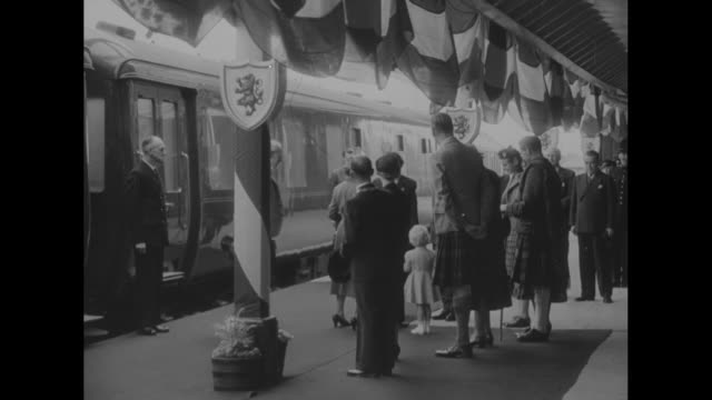 """camera on the world"" / title: ""royal family on a holiday in scotland"" superimposed over people at train station / people standing in front of train... - train guard stock videos & royalty-free footage"