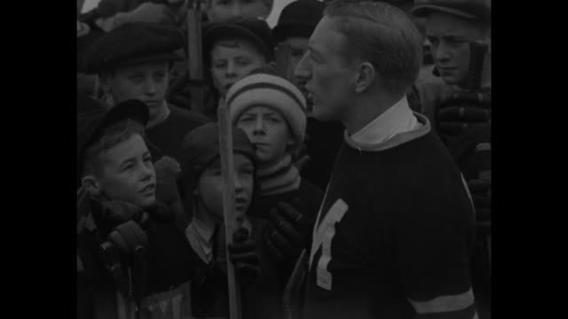 'Canada Builds Hockey Stars of the Future' / preteen and teen boys surround Montreal Maroons hockey player Russell Blinco near outdoor ice rink...