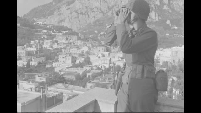 """capri, allies take over famed italian isle"" / soldier on rooftop looks through binoculars at the town of capri below / shoreline with houses and... - italian culture stock videos & royalty-free footage"