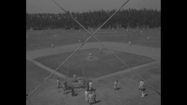 'Champions Yankees Limber Up For Pennant Race' / high angle wide shot baseball diamond thru backstop fencing New York Yankees practice game in...