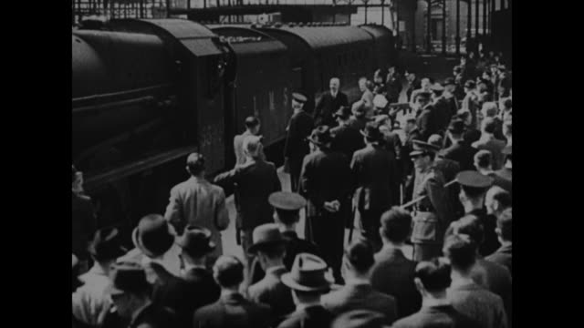 """churchill - england's leader returns from us"" / train pulls to a stop at london train station as large crowd stands on platform / british prime... - station stock videos & royalty-free footage"
